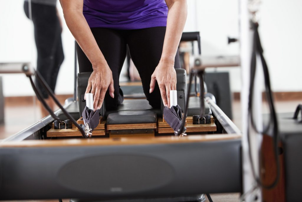 image of woman kneeling on the Pilates reformer