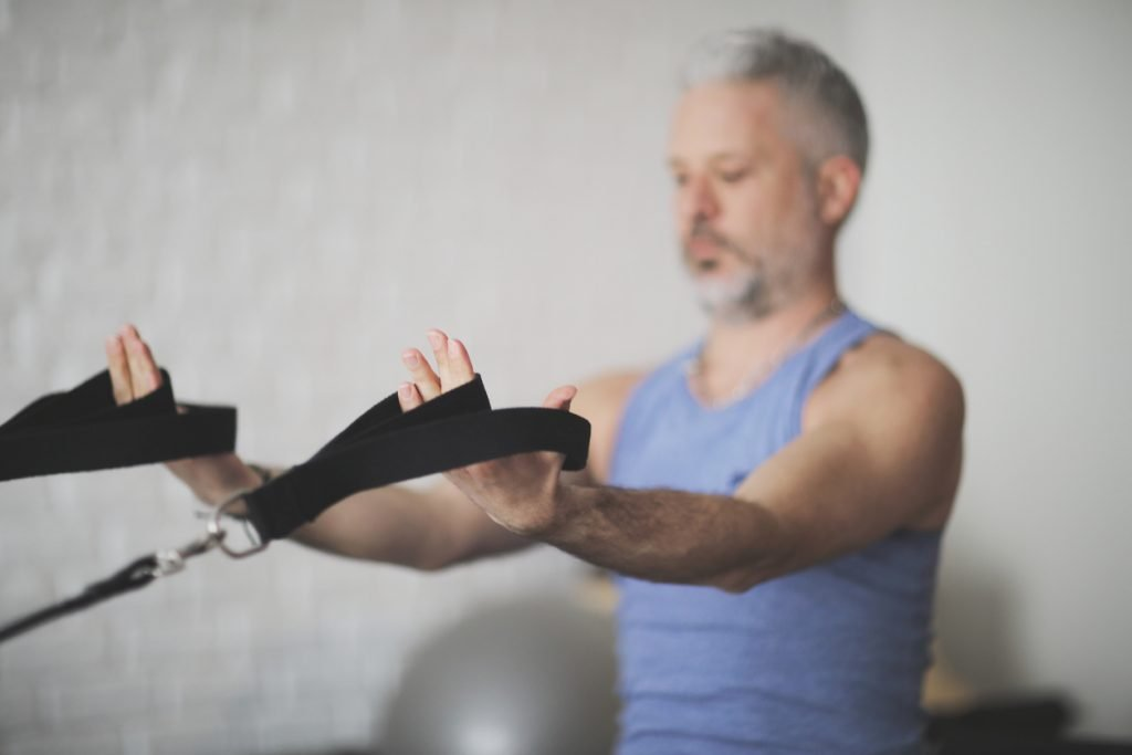 image of a man holding onto Pilates reformer straps